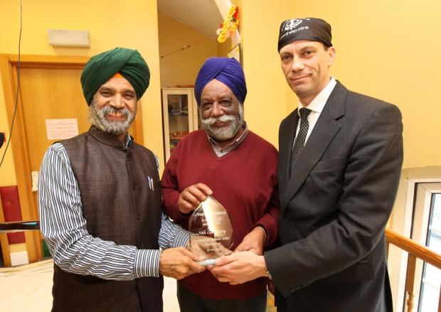 Martin Masters, right, receives the award from Gurbachan Singh Bhakar and Avtar Singh