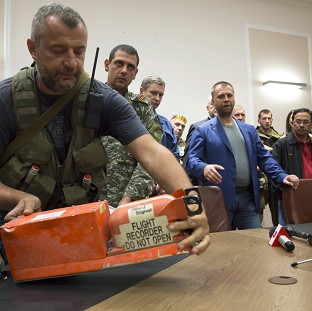 A pro-Russian fighter hands a black box from the crashed Malaysia Airlines plane over to Malaysian representatives in the city of Donetsk, eastern Ukraine (AP)
