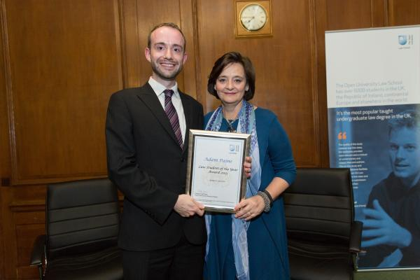 Adam Paine receiving his certificate from Cherie Blair.