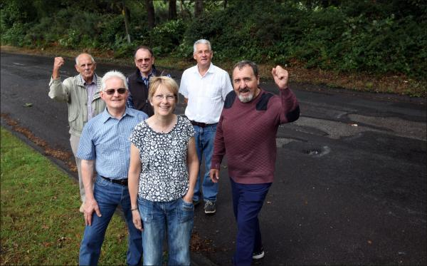 Delighted residents and councillors celebrate the city council's U-turn over potholes