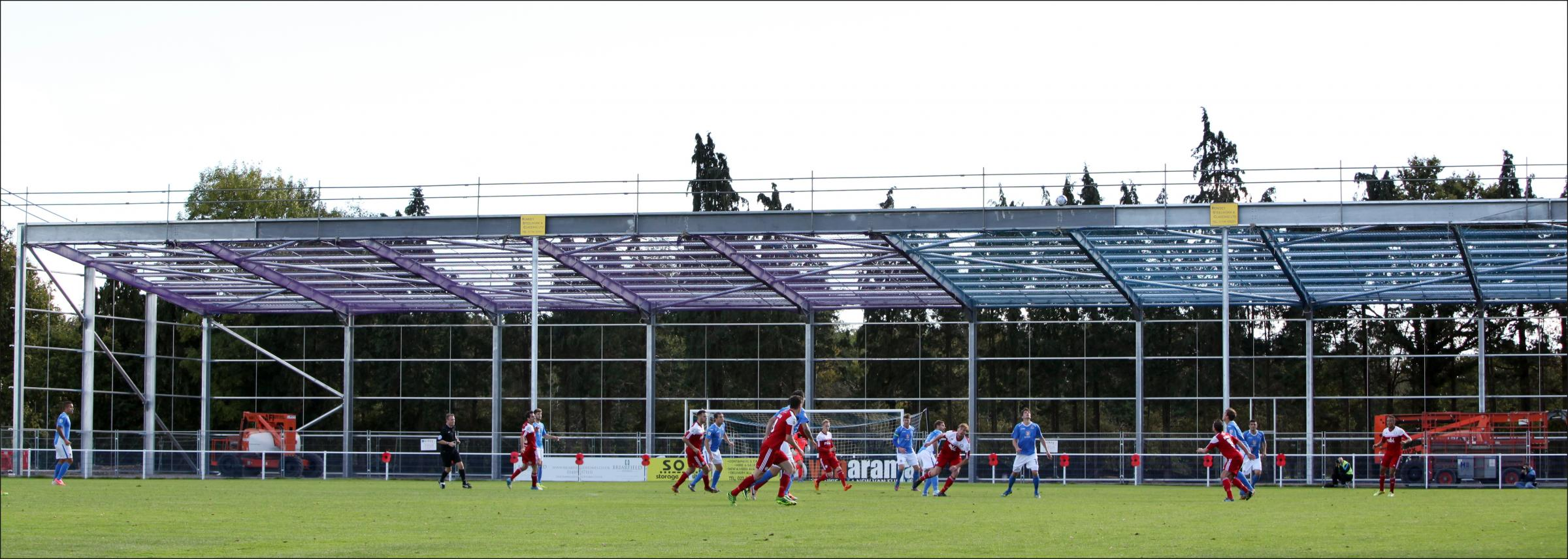 Eastleigh in action in front of their new stand at the Silverlake Stadium as it started to take shape during construction