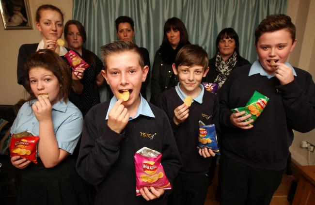 Harry Caws, 13, front, and his school mates and their mothers with their crisps
