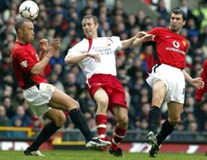 BATTLER: Brett Ormerod puts the heat on Mikael Silvestre, left of picture, and Roy Keane.