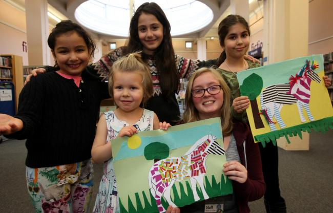 L-r, Runica Hesami-Kermani, 7, Leela Day, 3, Raha Radparvar, 8, and Heliya Naderi, 7, with library asisstant Lousie Lancashire. Zany Zebra workshop, Portswood Library, where children were invited to come up with a zebra design