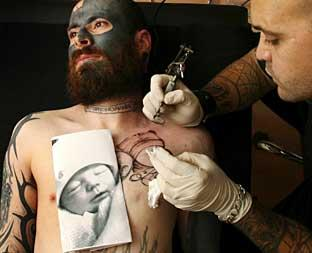 PERMANENT REMINDER: Freddie being tattooed by Paul Caruana of Pauly's Tattoos in Southampton (Riley's photograph is shown on Freddie's chest).