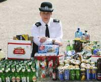 SHOCKING: Police officer Kerry Loveless, pictured at Shirley police station with bottles and cans of booze taken off kids drinking in the streets.