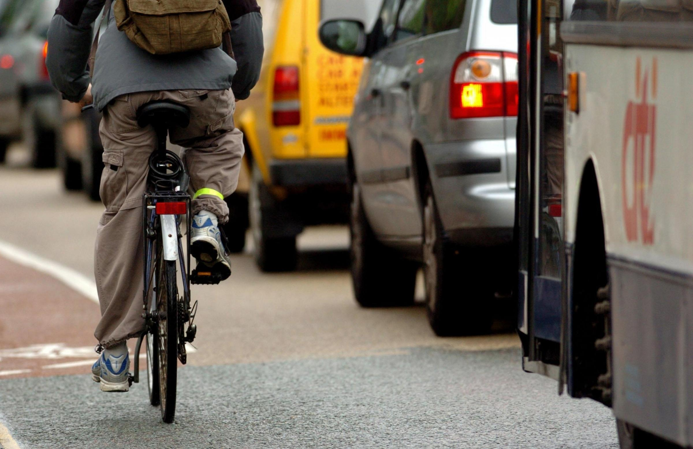 File photo dated 08/05/06 of a cyclist next to heavy traffic in Cambridge. PRESS ASSOCIATION Photo. Issue date: Thursday December 3, 2009. Cycling in England is much more hazardous than car travel, with June the worst month for those on two wheels, accord