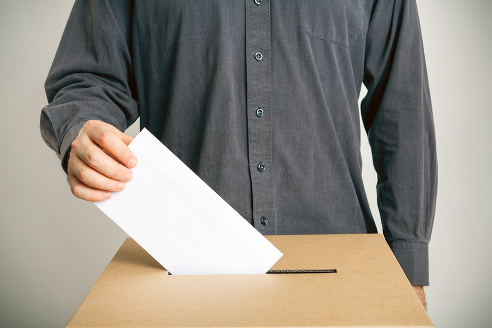 Stock photo of a voter casting their ballot