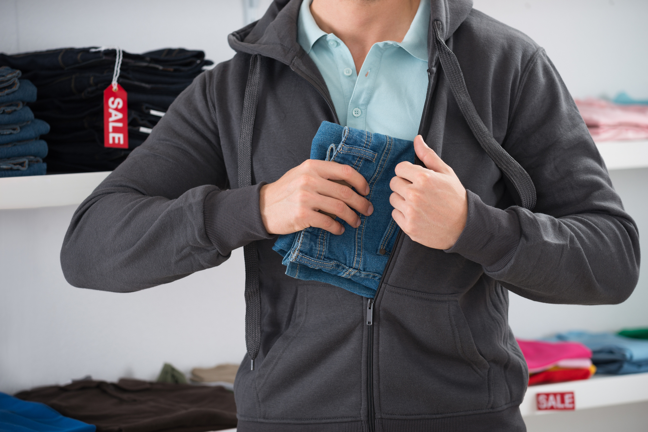 Midsection of man hiding jeans in jacket at store.