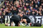 Adam Lallana, centre, receives treatment for a muscle injury suffered at Crystal Palace (Adam Davy/PA)