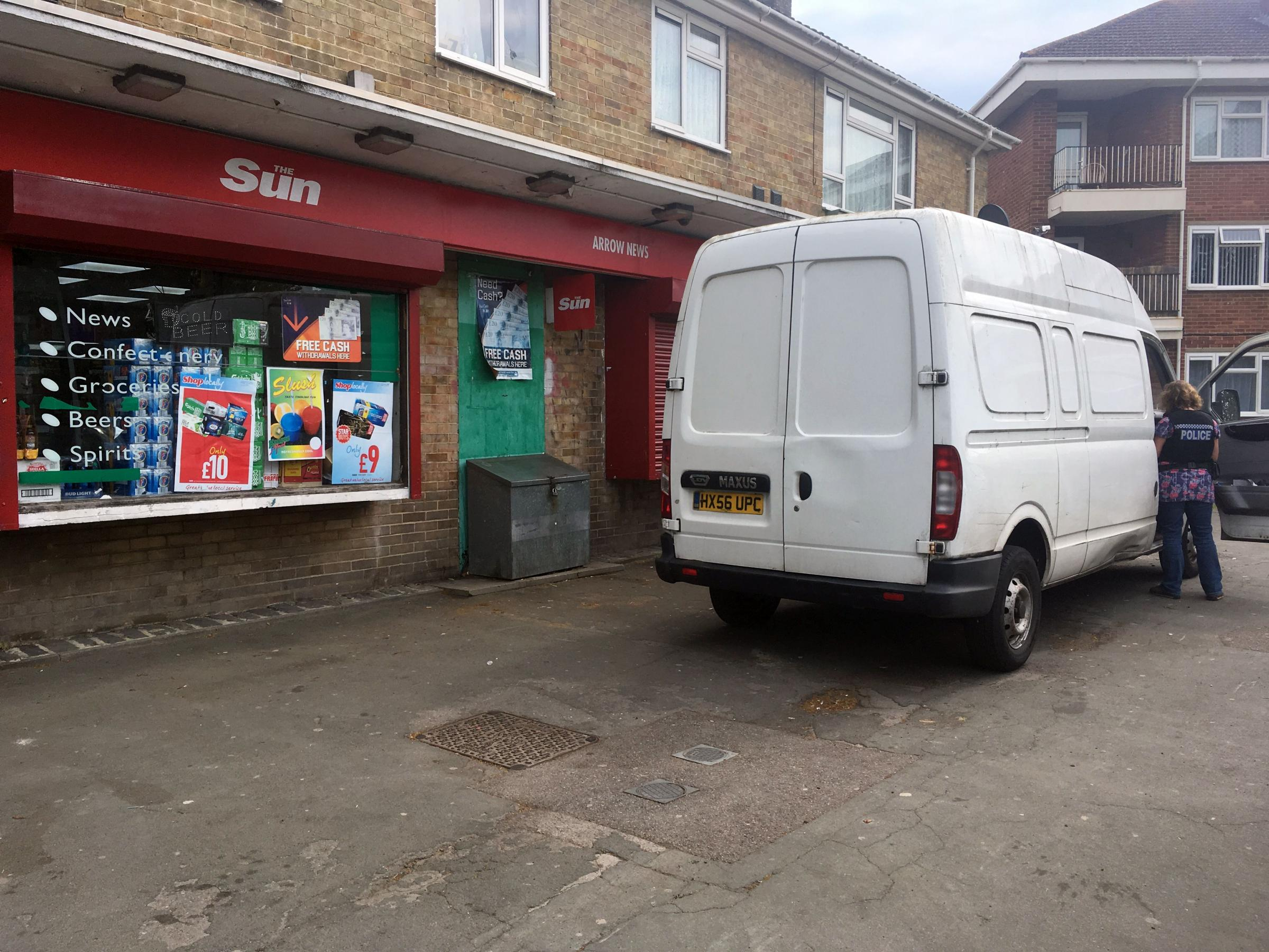 Police inspect a van outside the shop