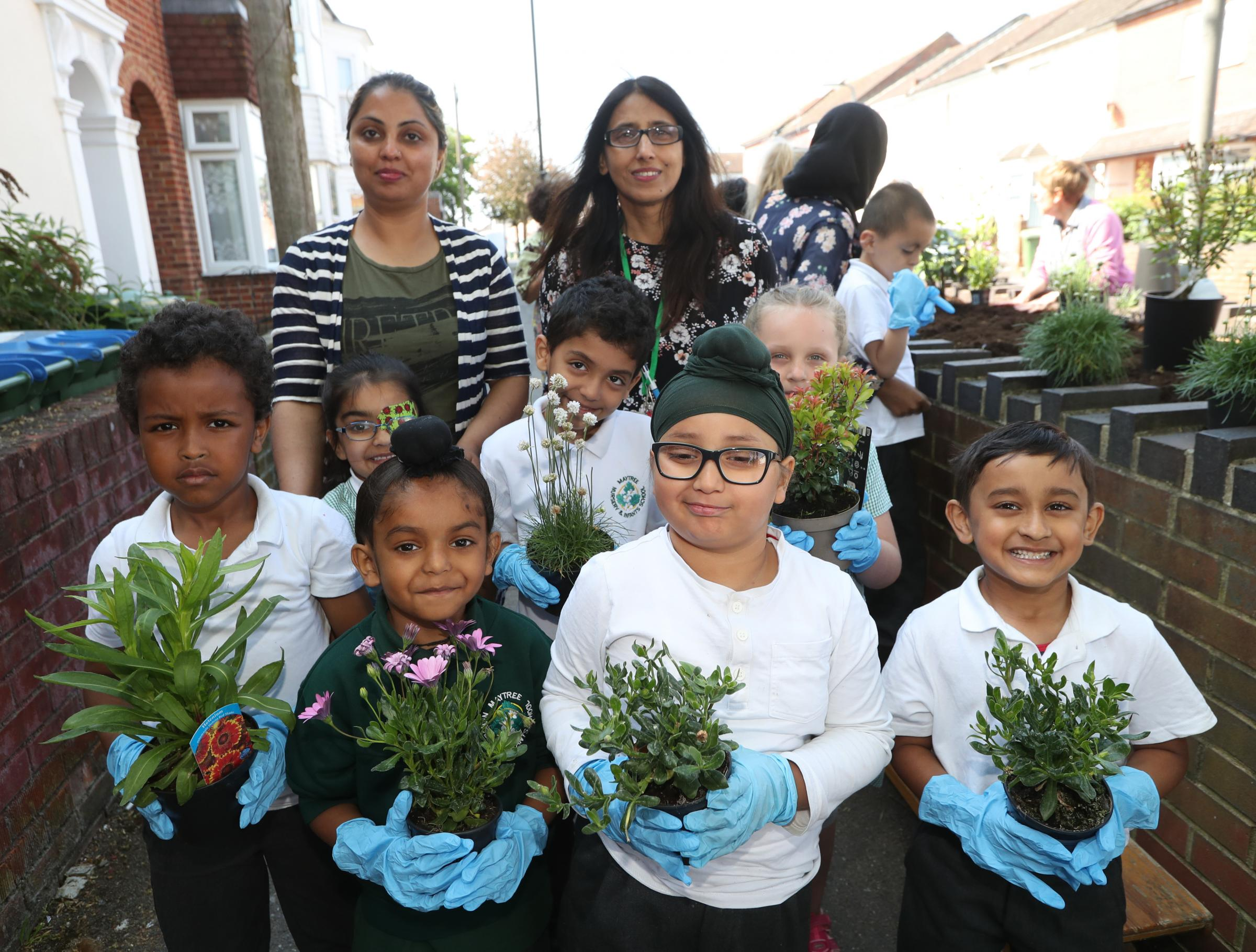 Pupils from Maytree Infant and Nursery School planting flowers in Derby Road with the help of teachers, parents and Councillor Satvir Kaur.