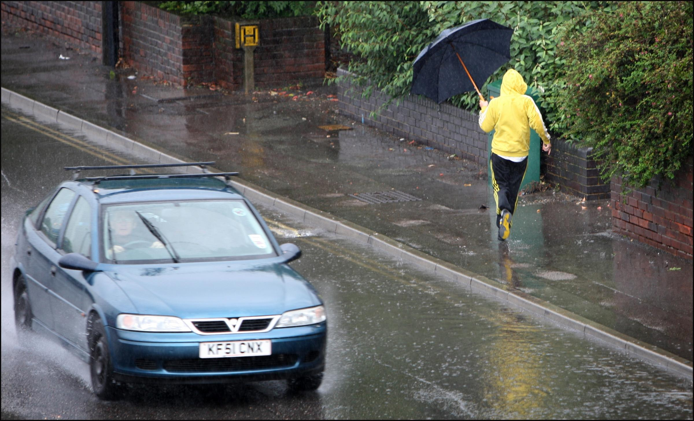 A pedestrian walks through flooded Millbrook Road West in Southampton following heavy rain (stock photo)
