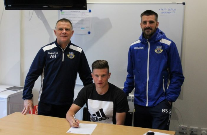 Ollie Dennett signs his pro contract for Eastleigh, flanked by manager Andy Hessenthaler (left) and assistant Ben Strevens