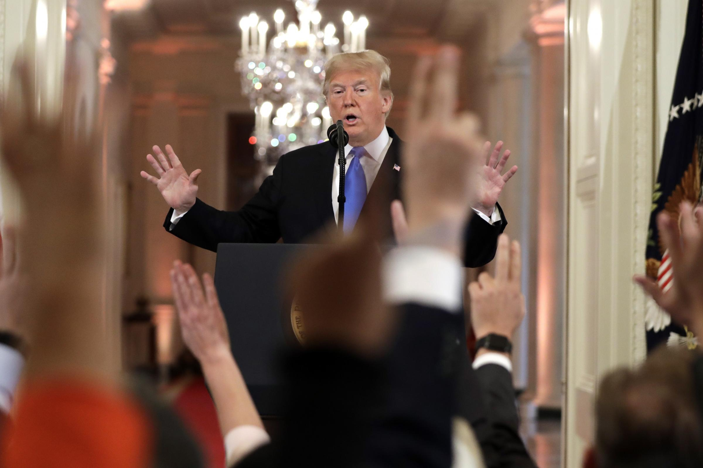 President Donald Trump reacts as reporters raise their hands to ask questions