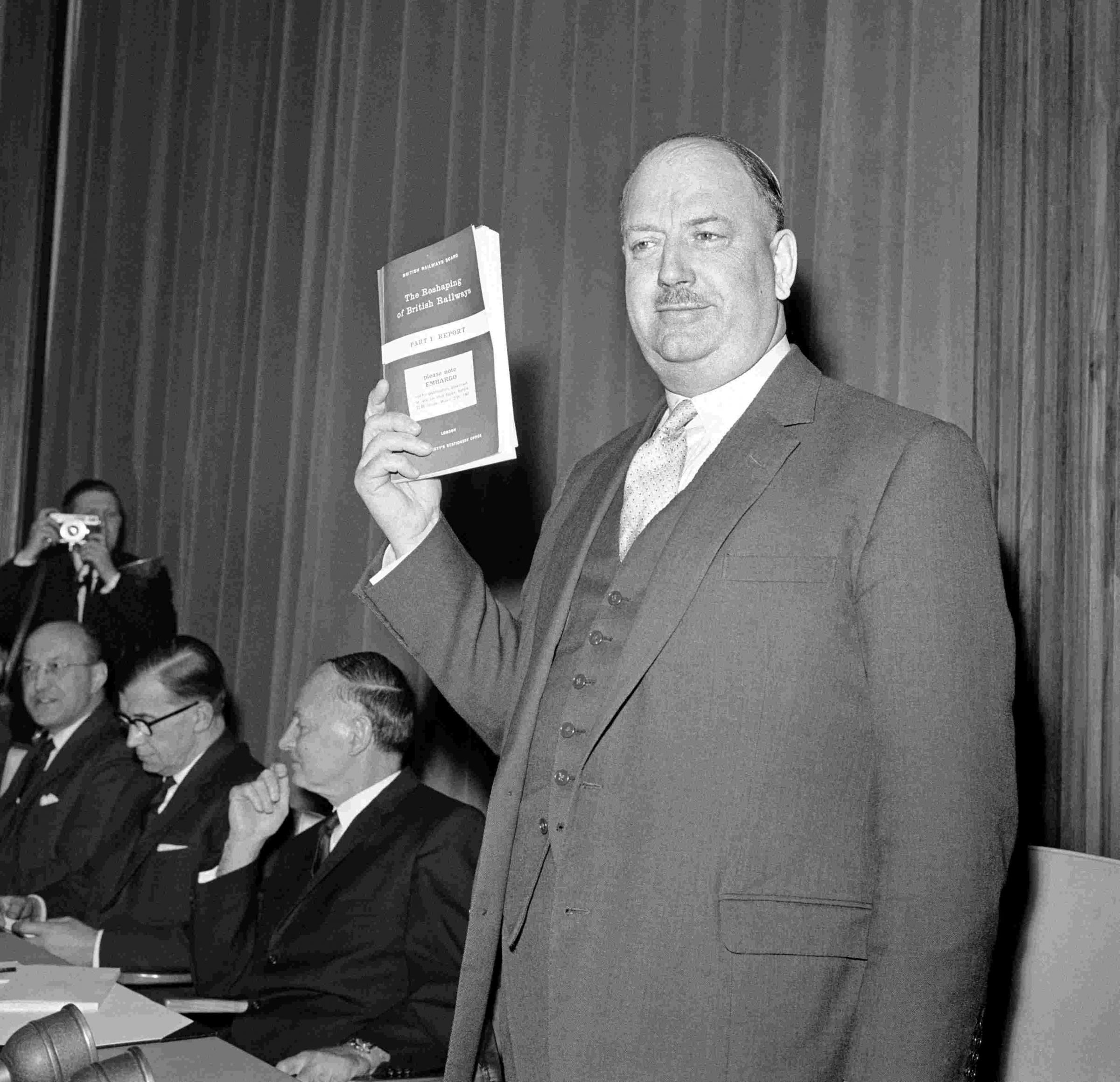 File photo dated 27/03/63 of Dr Richard Beeching holding aloft a copy of the pamphlet 'The Reshaping of British Railways', in Marylebone, London. This month marks the 50th anniversary of Dr Beeching's infamous report which gave the English lan