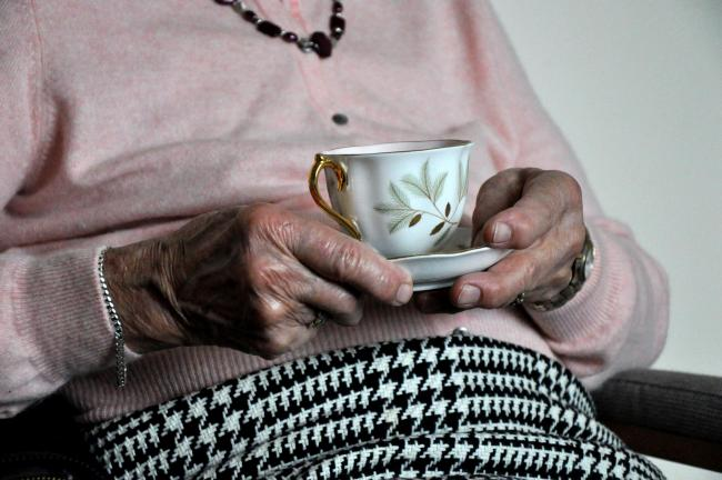 An elderly woman holding a cup of tea..