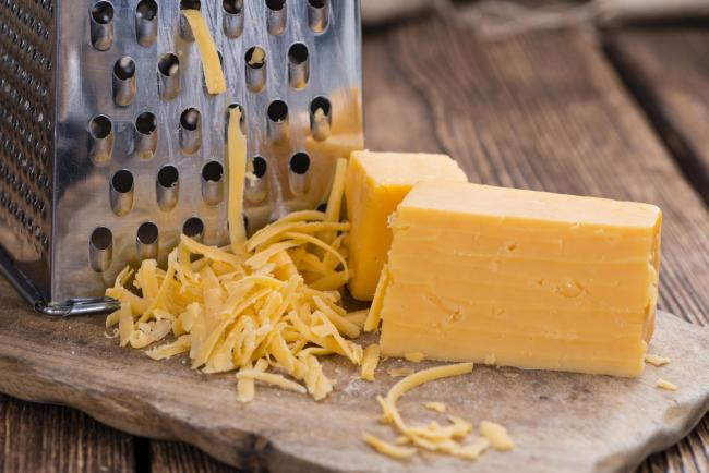 Grated Cheddar Cheese on rustic wooden background.